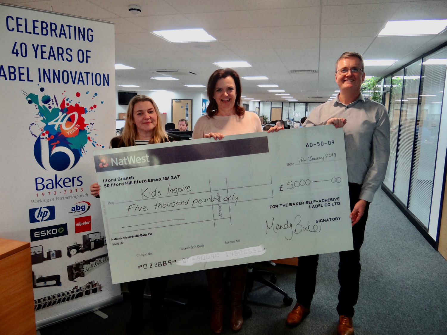 Baker labels present cheque to Kids Inspire